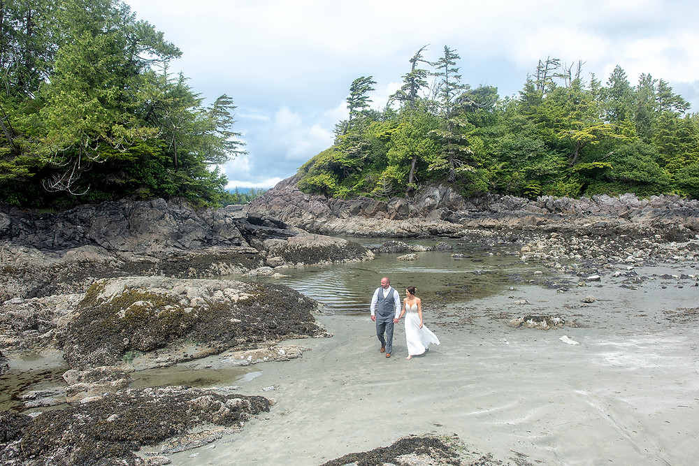 Married couple walks on the beach together holding hands at their Newly weds kiss in the forest at an Couple embraces in the fporest at an Bride and groom have their first kiss at an Beautiful beach ceremony at an Bride and groom hold rings during an elopement in Tofino. Photographed by Kaitlyn Shea.