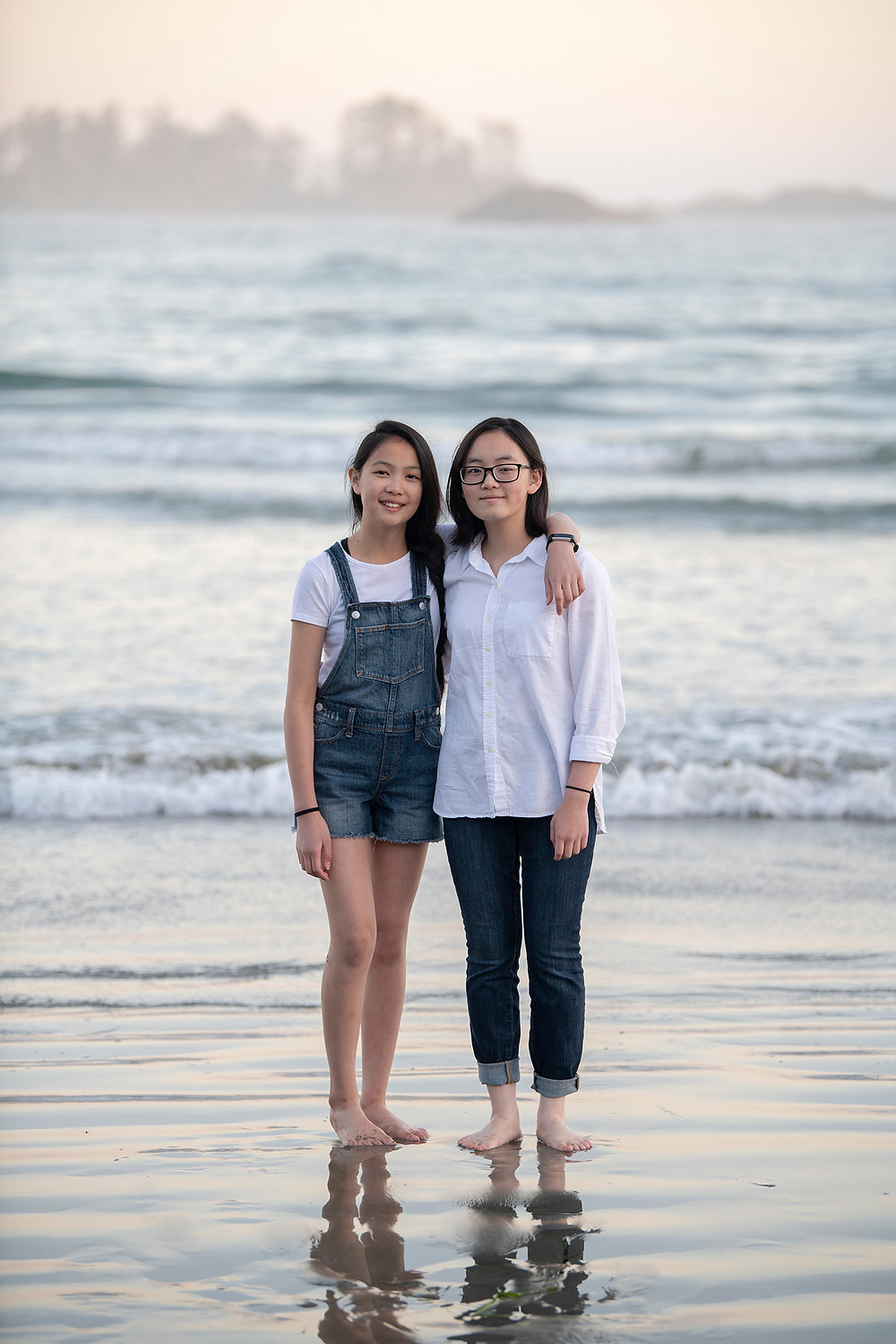 sisters smile for the camera during family photos in Tofino | Photographed by Kaitlyn Shea