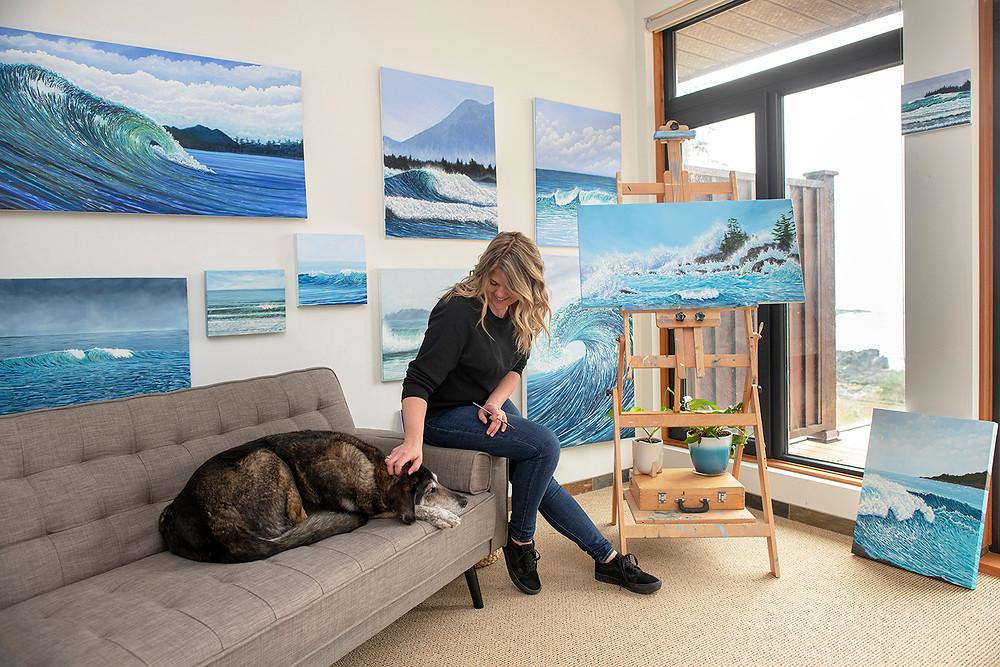 Tofino artist Emma Paveley pets her dog in her studio