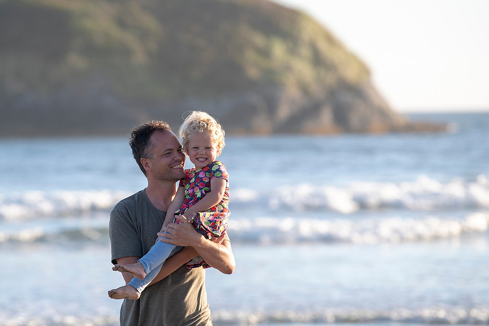 Father and daughter on the beach during their family photos in Tofino. Photography by Kaitlyn Shea.