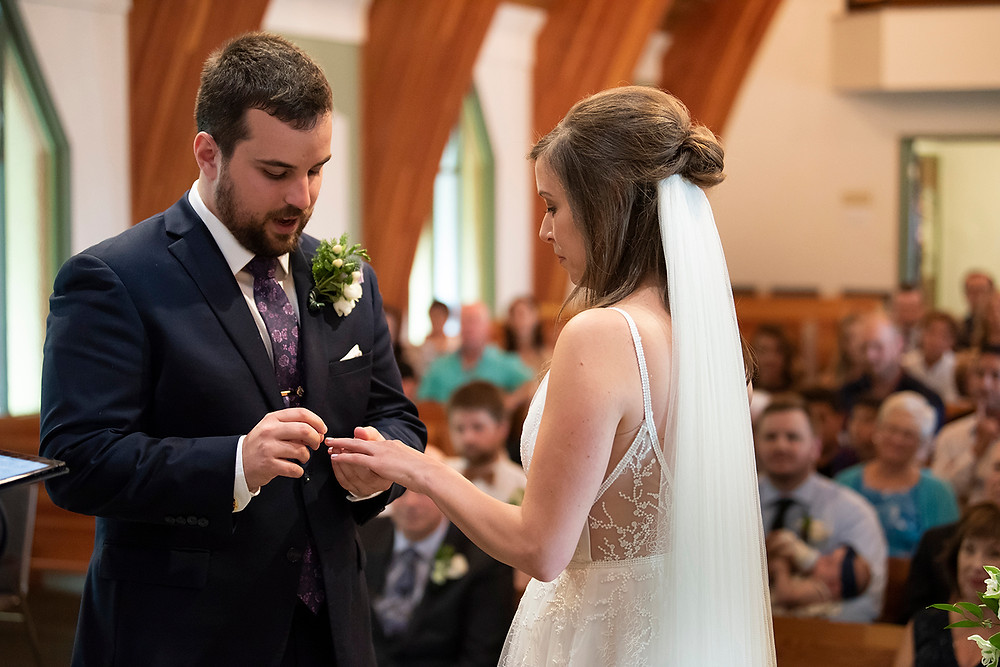 Groom places ring on brides finger at Vancouver Island wedding. Photographed by Kaitlyn Shea.