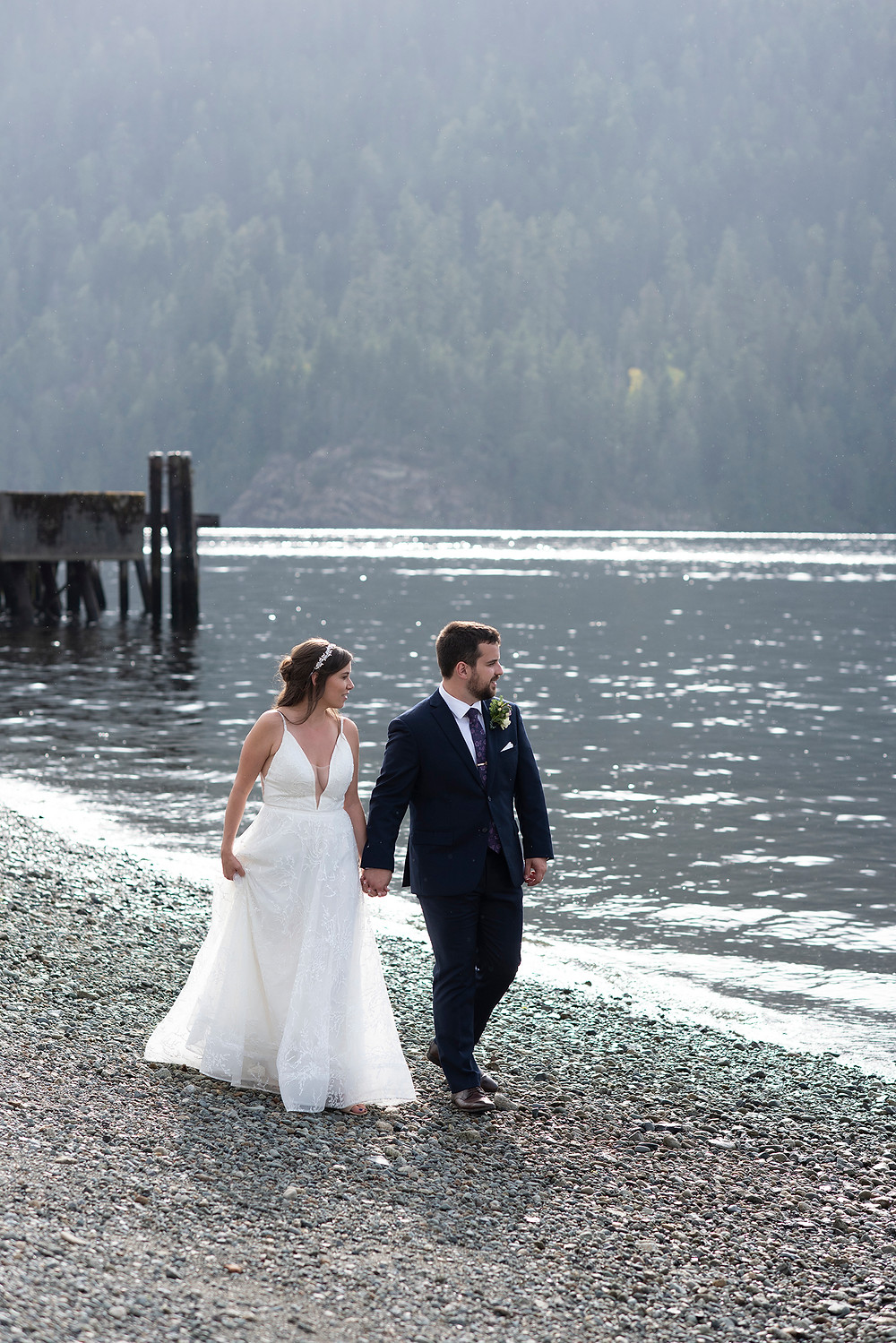 Newly married couple walks on the beach at their August wedding on Vancouver Island. Photographed by Kaitlyn Shea.