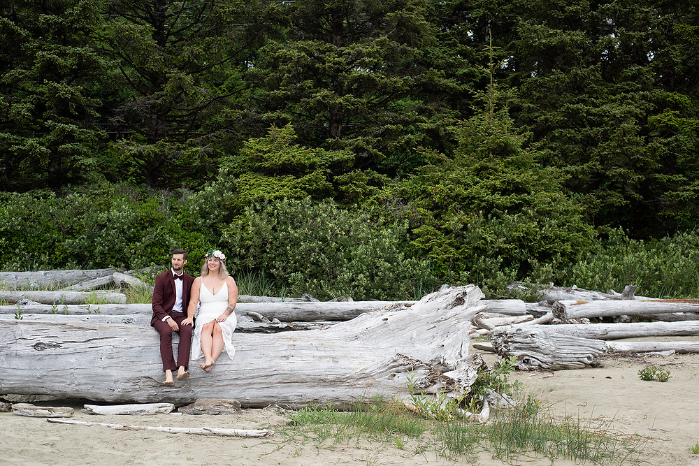 Couple sits on log at Tofino vow renewal. Photographed by Kaitlyn Shea.