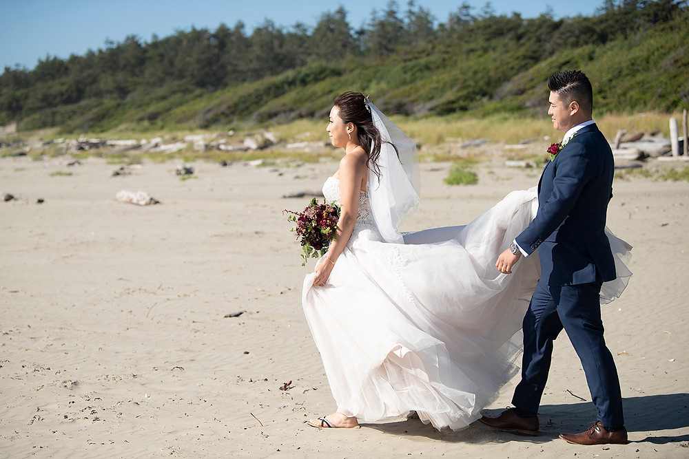 Bride and groom walk on Wickaninnish Beach at their Ucluelet wedding at Black Rock Resort. Photographed by Ucluelet Photographer Kaitlyn Shea.