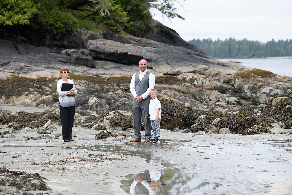 Groom and his son stand and wait for the bride at an elopement in Tofino. Photographed by Kaitlyn Shea.