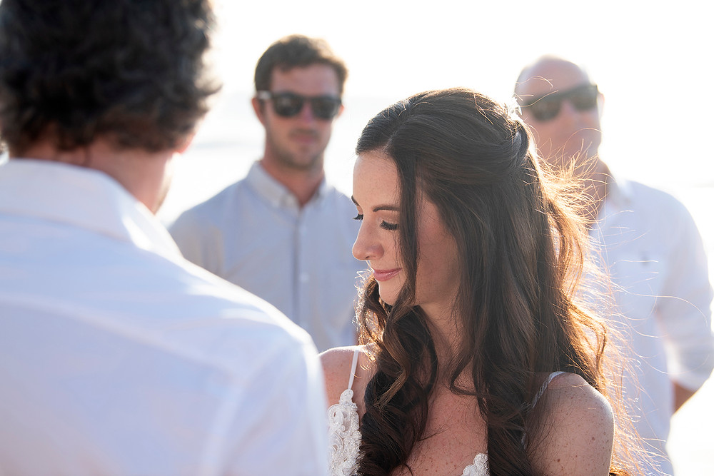 Bride stands on the beach with the sun in her hair at her destination wedding in Playa Grande, Costa Rica. Photographed by Kaitlyn Shea.