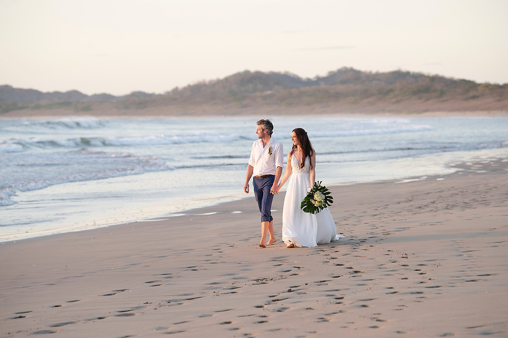 Couple walks hand in hand on the beach at sunset at their destination wedding in Playa Grande, Costa Rica. Photographed by Kaitlyn Shea.