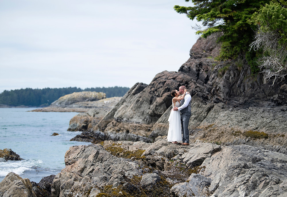 Married couple kisses on the rocks at MacKenzie Beach at an Couple embraces in the fporest at an Bride and groom have their first kiss at an Beautiful beach ceremony at an Bride and groom hold rings during an elopement in Tofino. Photographed by Kaitlyn Shea.