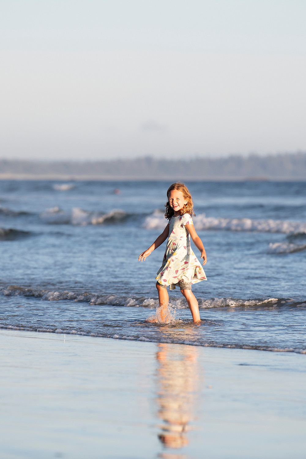 Girl smiles while walking in the water at Long Beach in Tofino. Photographed by Kaitlyn Shea.
