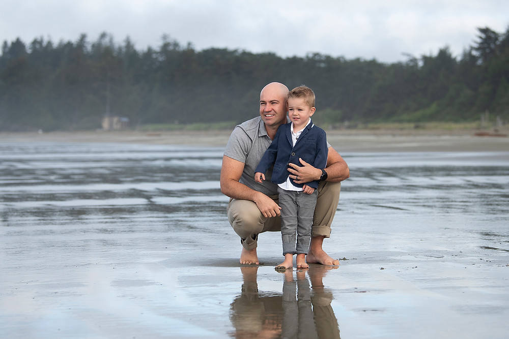 Father and son stand together on Long Beach during a family photography session. Photographed by Kaitlyn Shea.
