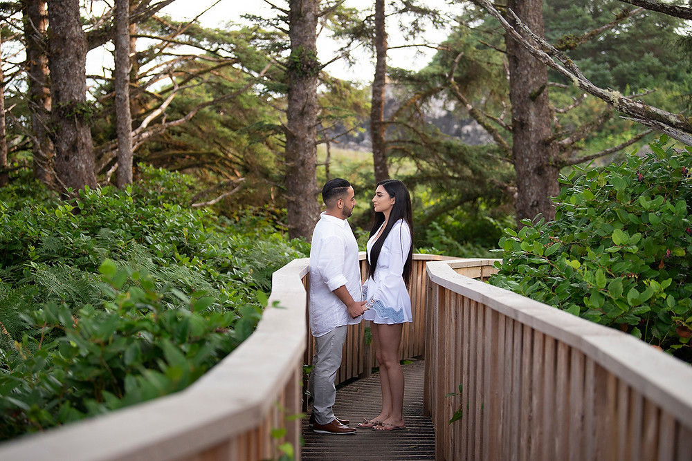 Couple standing on board walk at Pettinger Point after surprise proposal in Tofino.