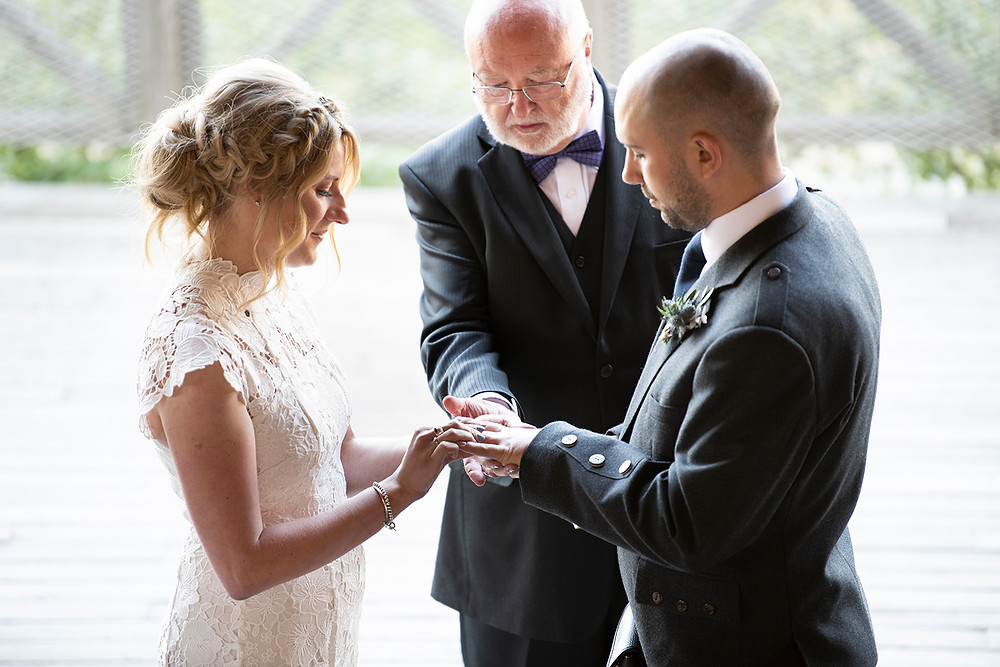 Bride places wedding ring on grooms finger during ceremony at Sea Cider on Vancouver Island.