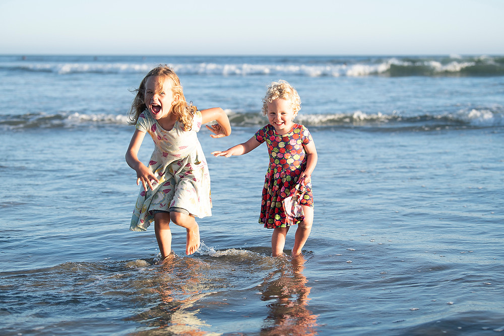 Sisters run through the water during Tofino family photos. Photographed by Kaitlyn Shea.