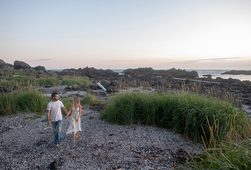 Couple walks hand in hand on Big Beach during their Ucluelet engagement photos. Photographed by Tofino photographer Kaitlyn Shea.