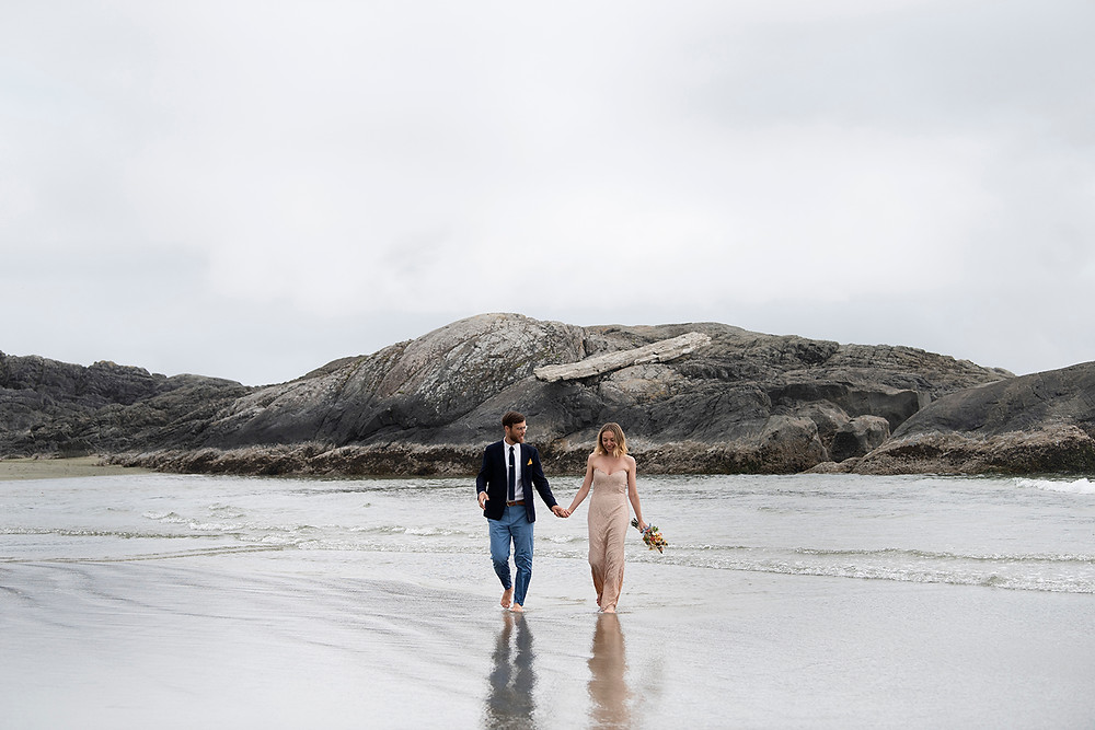 Happy couple walks on the beach at their Tofino beach elopement. Photographed by Kaitlyn Shea.