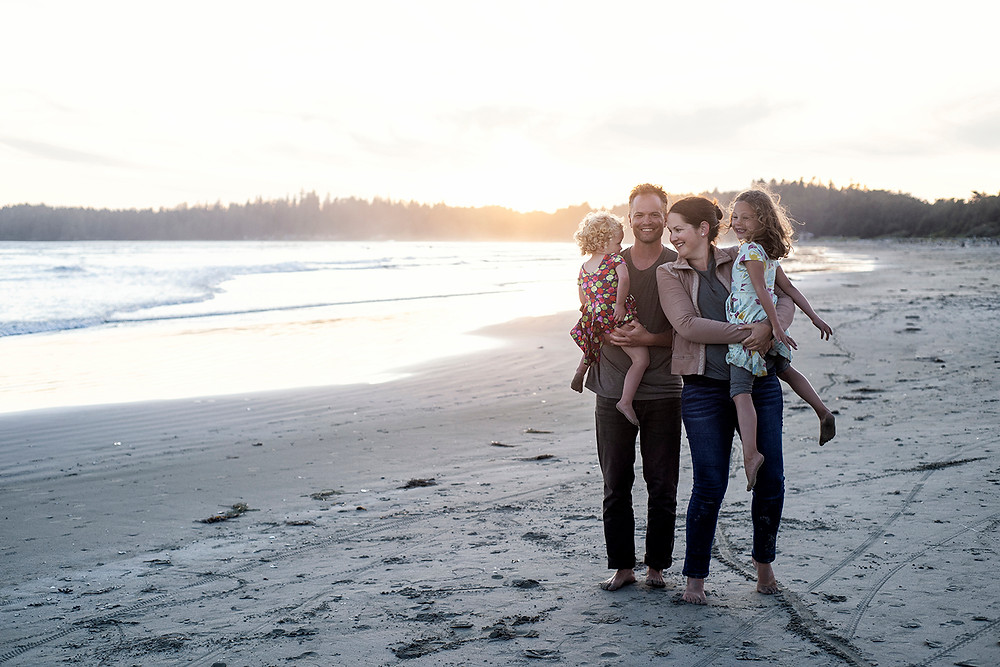 Family stands together with the sunset in the background during family photos in Tofino. Photographed by Kaitlyn Shea.