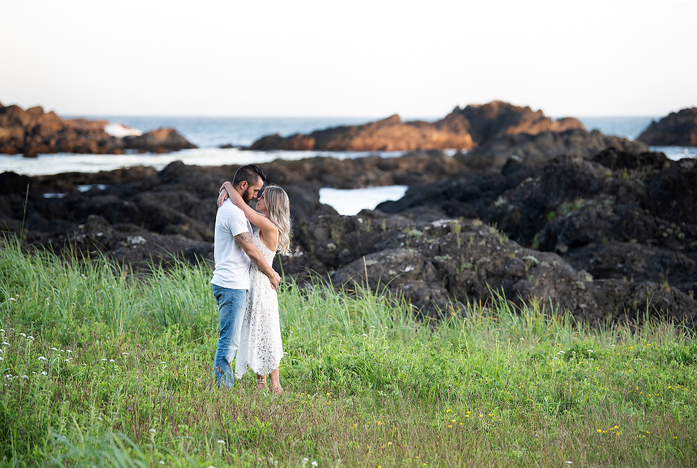 Man and woman hug on Big Beach in Ucluelet during their engagement photos. Photographed by Tofino photographer Kaitlyn Shea.