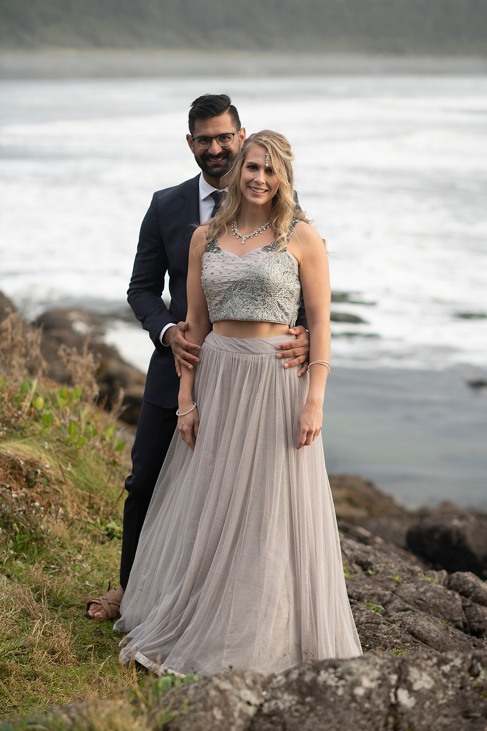 Couple stands together on Pettinger Point at their small wedding in Tofino. Photographed by Tofino wedding photographer Kaitlyn Shea.