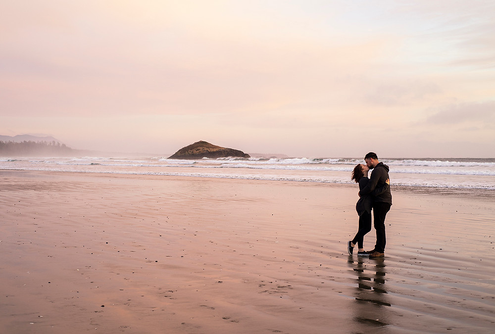 Couple kisses with Lovekin Rock in the background during their Tofino engagement photos. Photographed by Tofino photographer Kaitlyn Shea.