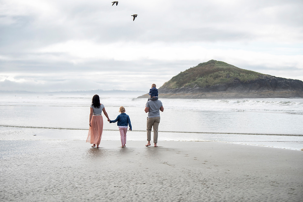Family walks toward Lovekin Rock during their family photography session in Tofino. Photographed by Kaitlyn Shea.