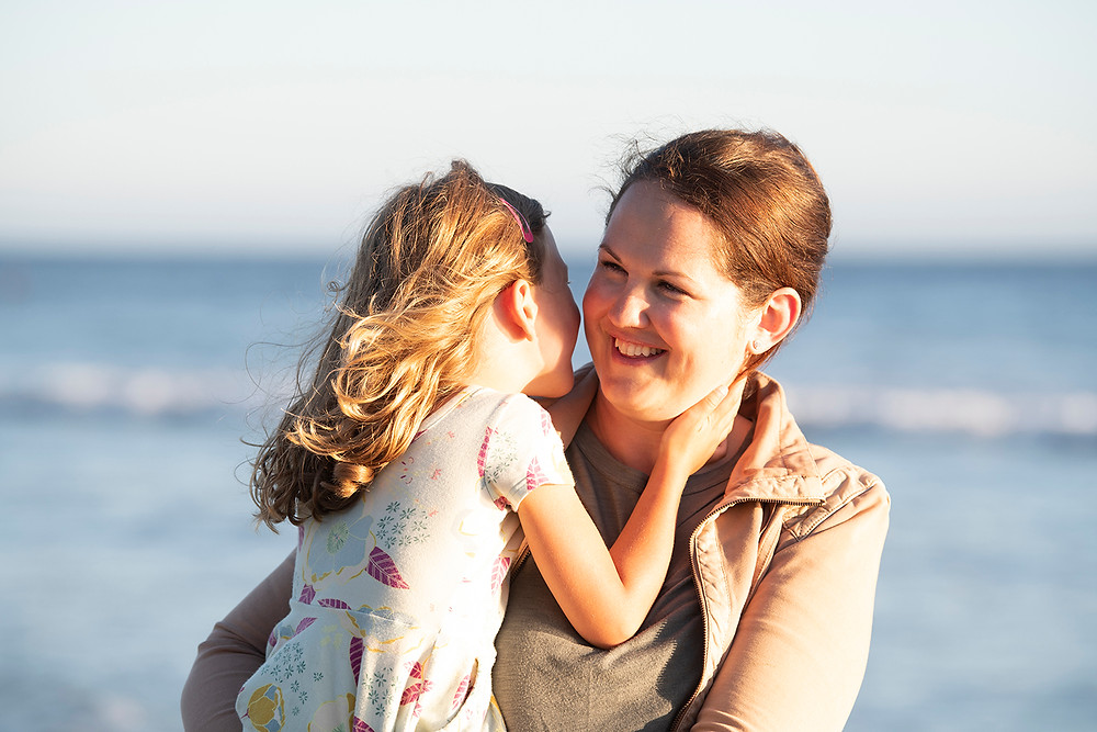 Mother and daughter on the beach during their family photos in Tofino. Photographed by Kaitlyn Shea.