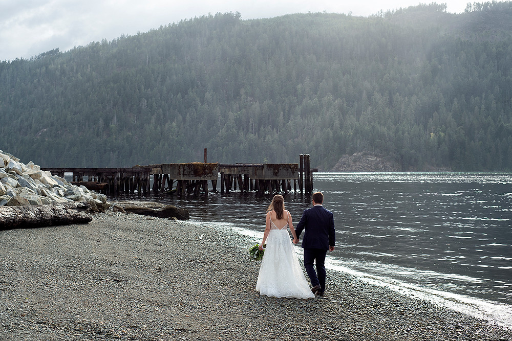 Bride and groom stroll on the beach holding hands at their August wedding on Vancouver Island. Photographed by Kaitlyn Shea.
