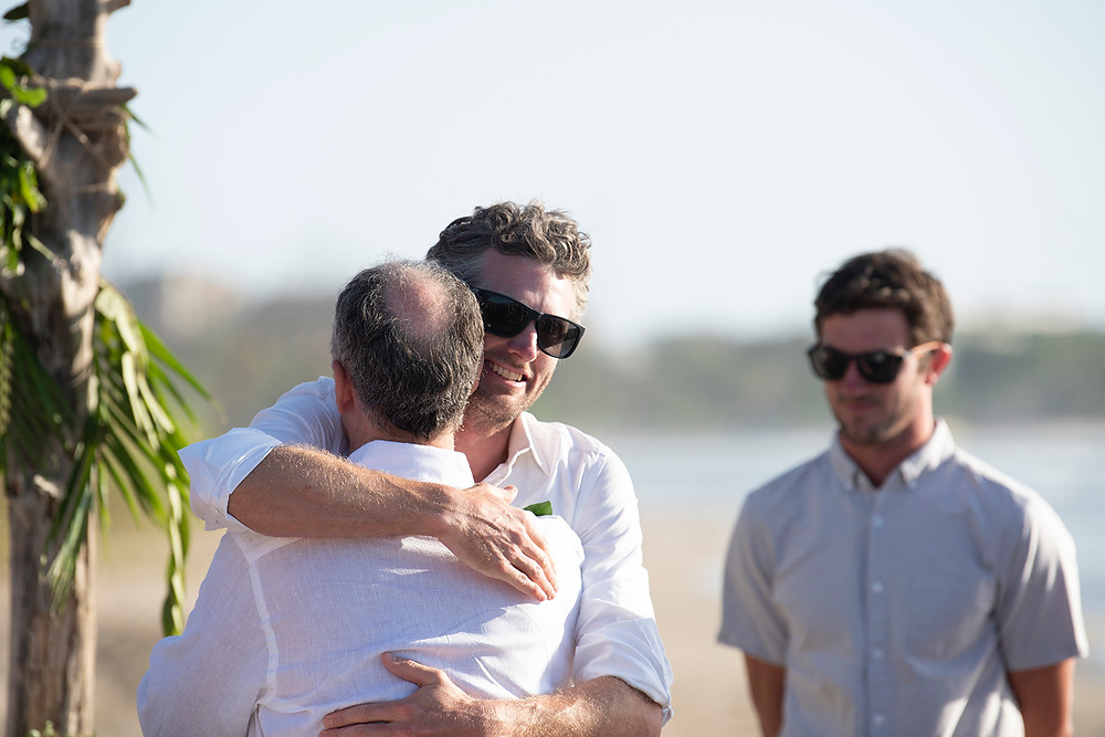 Groom hugs father of the bride at a destination wedding in Playa Grande, Costa Rica. Photographed by Kaitlyn Shea.