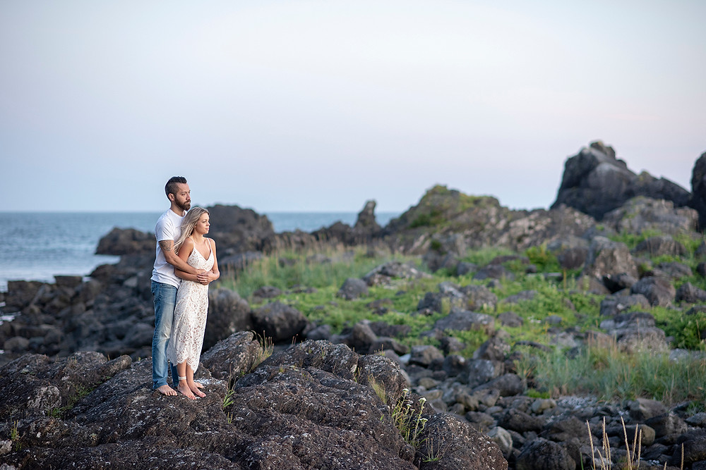 Couple stands on rocks together with sunset behind them during their engagement photos in Ucluelet. Photographed by Tofino photographer Kaitlyn Shea.