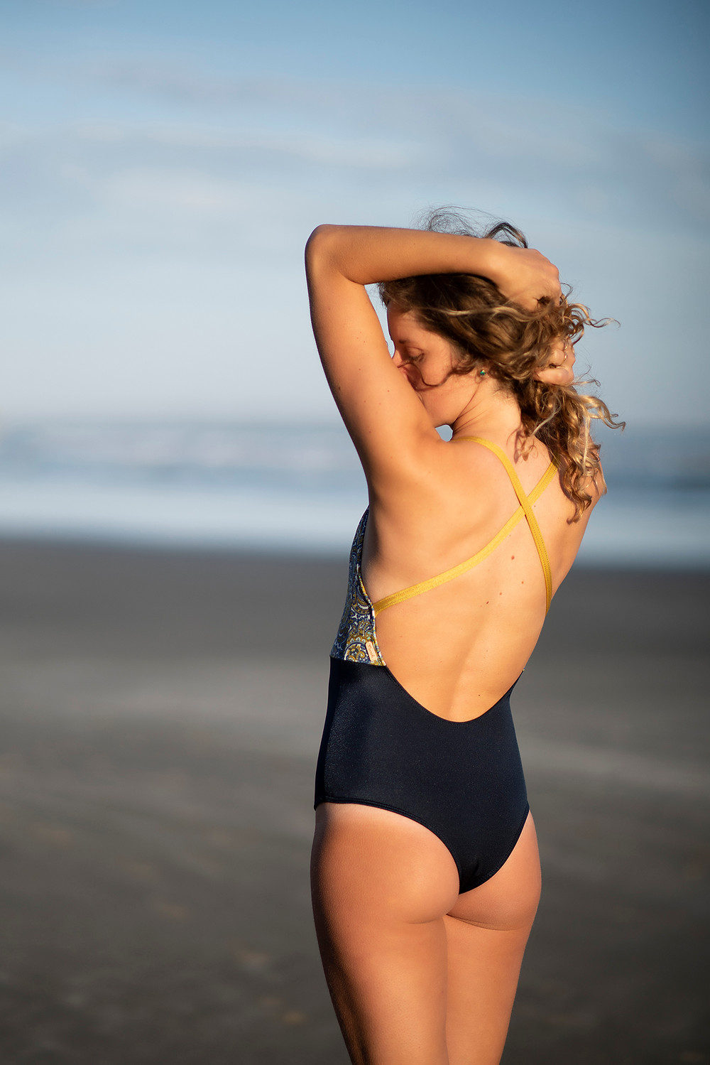 Girl stands on Long Beach in Tofino wearing her Monaia swimsuit. Photographed by Kaitlyn Shea.