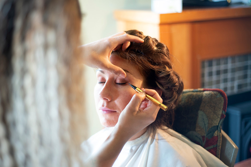 bride gets her makeup done at Long Beach Lodge wedding in Tofino. Photographed by Kaitlyn Shea