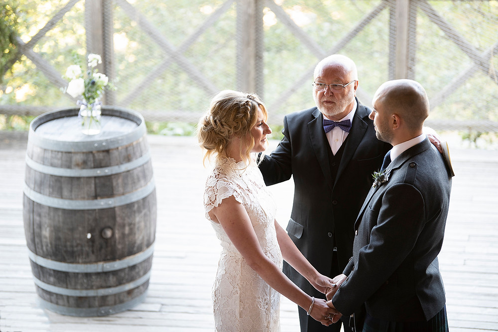 Couple joins hands during their wedding ceremony at Sea Cider Victoria. Photographed by Kaitlyn Shea.