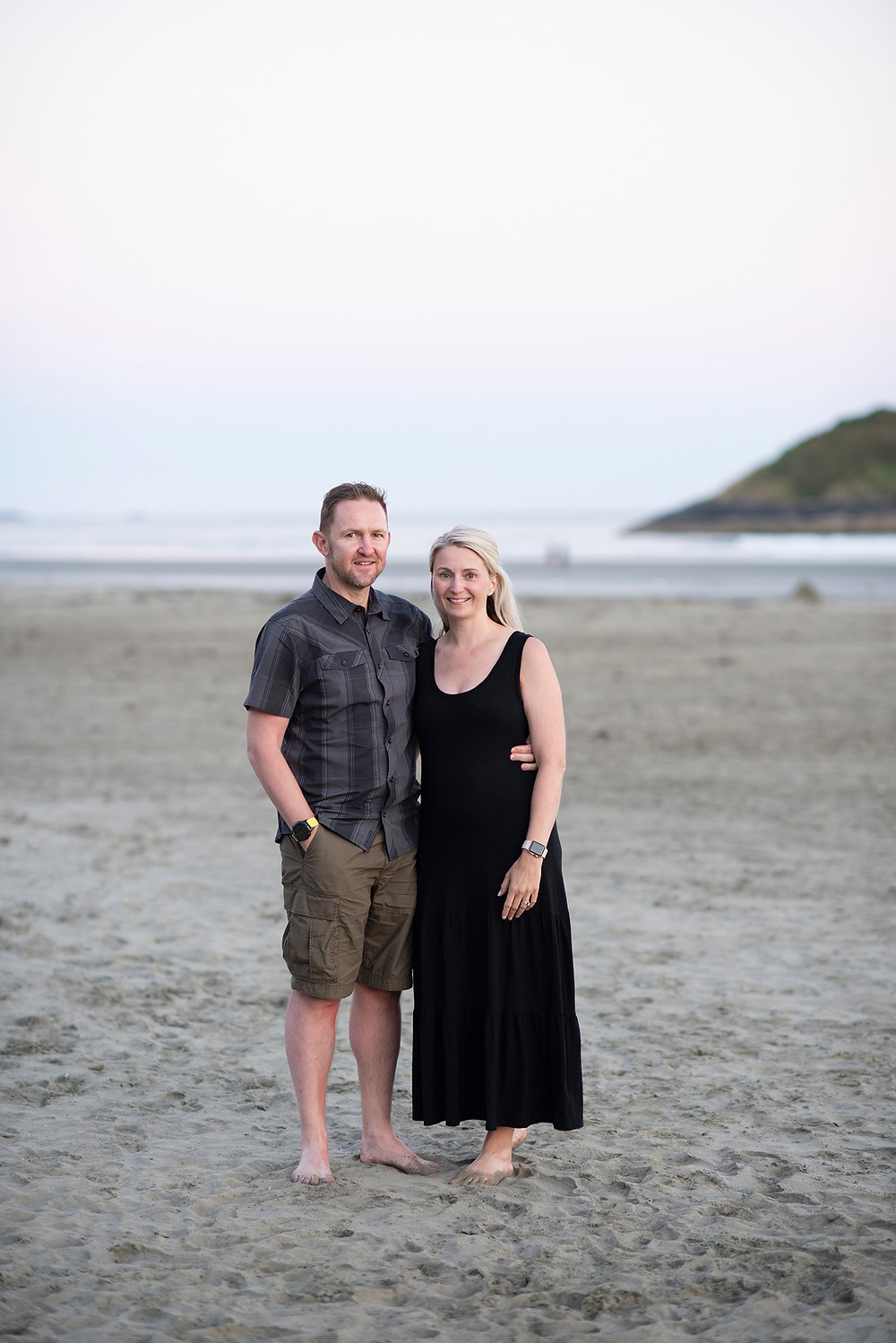 Parents stand together on the beach during family photos in Tofino. Photographed by Kaitlyn Shea.