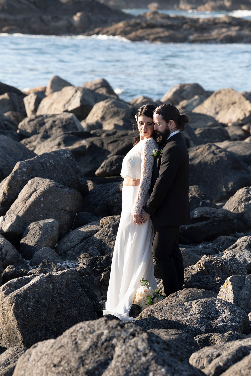 Man and wife stand by the ocean at their elopement in Tofino. Photographed by Kaitlyn Shea.