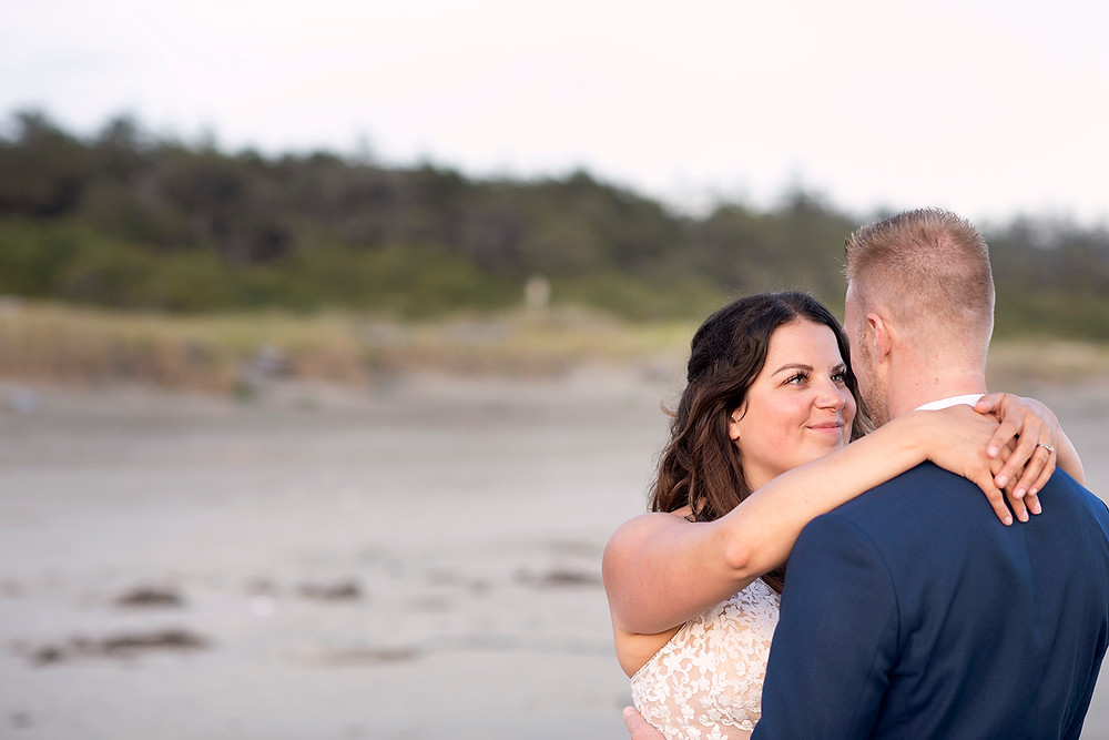Bride smiles at groom in sunset wedding photo session on the beach in Tofino. Photographed by Kaitlyn Shea.