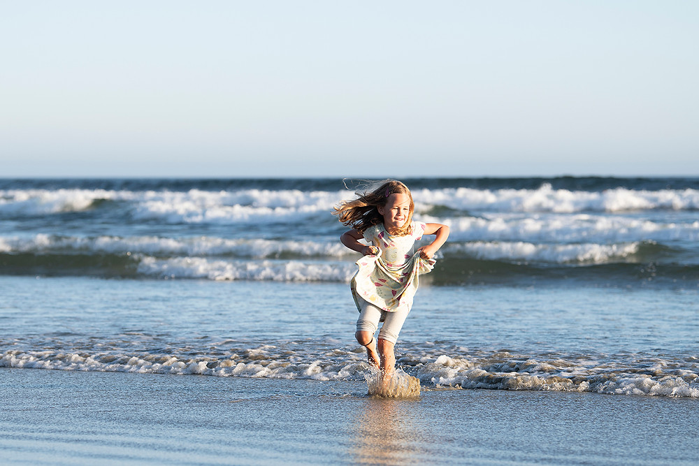 Little girl runs through the ocean during a family photography session in Tofino. Photographed by Kaitlyn Shea.