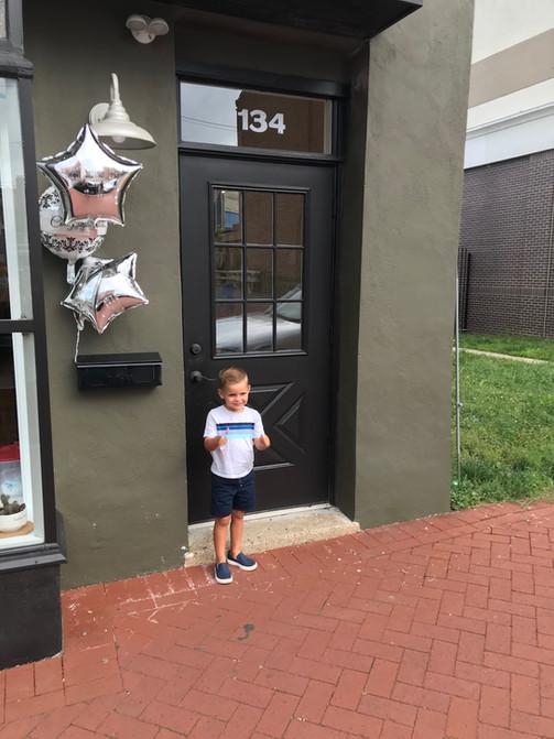 Boy outside The Shop on Market Street barbershop