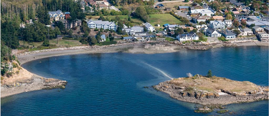 Landmark on Orcas Island from the sky. Fishing Bay and Indian Island are in the foreground, with the Landmark and Eastsound shops in the distance.