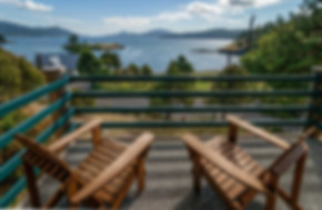 Two deck chairs overlook Fishing Bay from a water view unit of The Landmark Orcas Island.