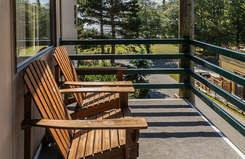 Two deck chairs sitting in the sun of a side view unit of Landmark Orcas Island. You can see the peekabo view of the bay in the distace.