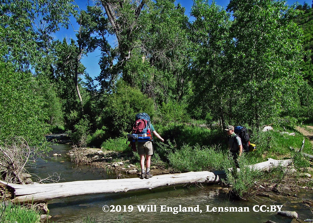 Boy Scout crossing a creek while another watches on for safety, Philmont 2016