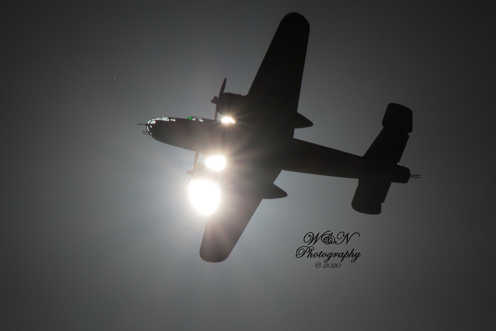 B25 Bomber flying over head, silhouetted against the sun