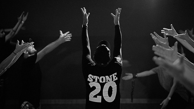 """Black & white photo of Tony Stone Teaching. He has his arms up and the back of his t-shirt reads """"Stone 20."""""""