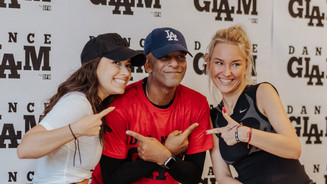 Tony with 2 of his sqaud members at an event in Europe. DanceGLAM red carpet background. They are all smiling.