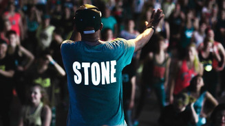 """Tony's back  with t-shirt that reads """"Stone."""" He is teaching a very large crowd."""