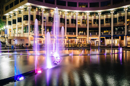 Fountains and buildings at night, in Geo