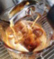 Iced Espresso Eiswürfel mit Espresso der aus einer Espressomaschine läuft