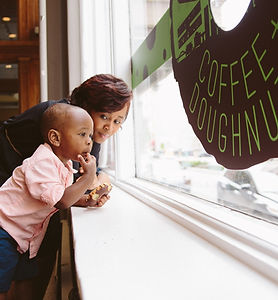 A child looking out a storefront window with a woman standing behind him.