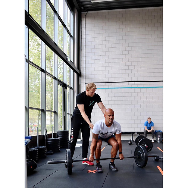 Coach Auke Muller correcting athlete in class at The Bar Rotterdam Functional Fitness Gym Personal Training Crossfit