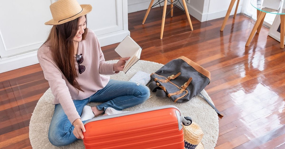 Girl reading a book and unpacking suitcase