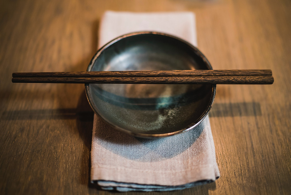 Wooden chopsticks resting on top of a bowl
